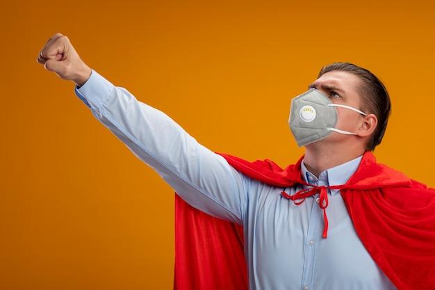 オレンジ色の背景の上に立って自信を持って見える勝利のジェスチャーを作る保護フェイシャルマスクと赤いマントのスーパーヒーローのビジネスマン