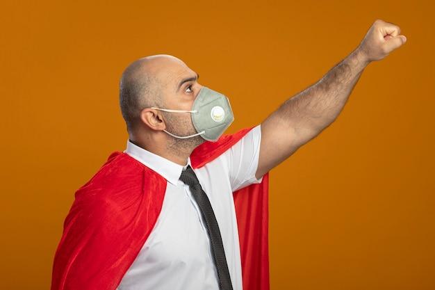 オレンジ色の壁の上に立って自信を持って見える勝利のジェスチャーを作る保護フェイシャルマスクと赤いマントのスーパーヒーローのビジネスマン