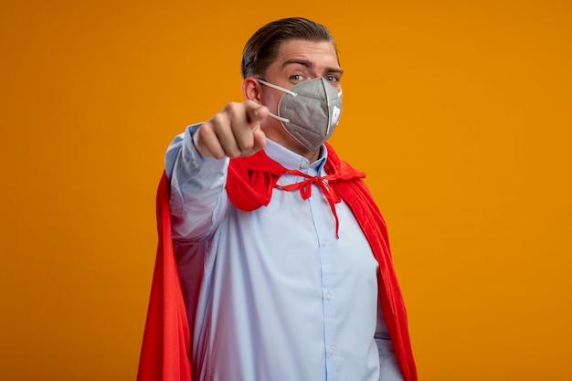 オレンジ色の背景の上に自信を持って立っているあなたを人差し指で指している保護フェイシャルマスクと赤いマントのスーパーヒーローの実業家