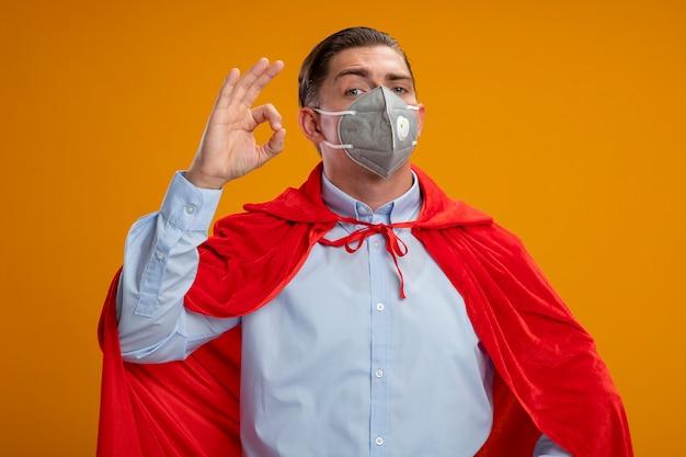 保護フェイシャルマスクと赤いマントのスーパーヒーローの実業家は、オレンジ色の壁の上に立っているokサインを示して幸せで前向きに笑っています