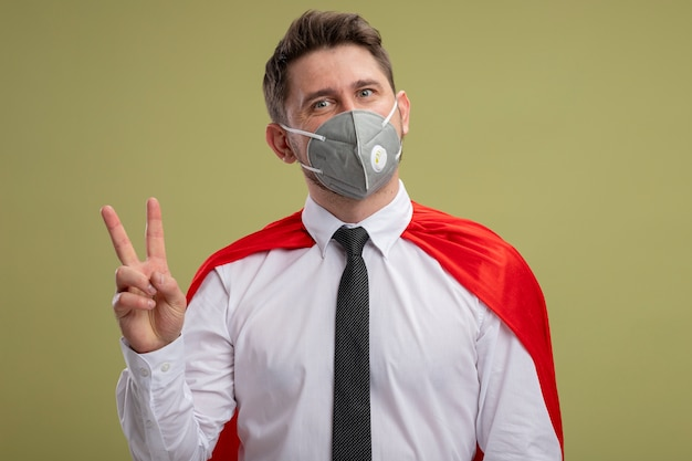 緑の壁の上に立っているv-サインを示す幸せでポジティブな笑顔の保護フェイシャルマスクと赤いマントのスーパーヒーローのビジネスマン