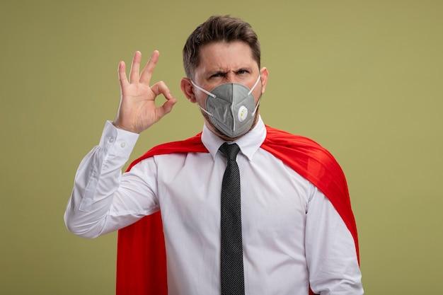 緑の壁の上に立っているokサインを示して笑顔の保護フェイシャルマスクと赤いマントのスーパーヒーローのビジネスマン