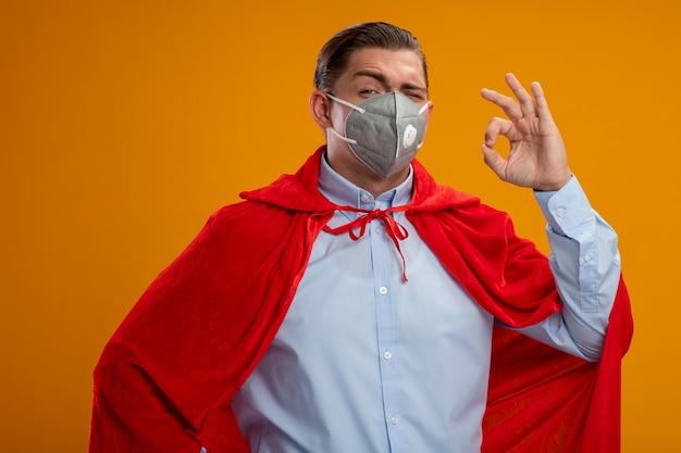 オレンジ色の壁の上に立っているokサインを示す笑顔の保護フェイシャルマスクと赤いマントのスーパーヒーローのビジネスマン