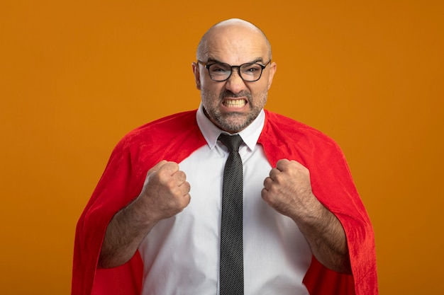赤いマントとメガネで拳を握りしめているスーパーヒーローのビジネスマンは狂った狂気