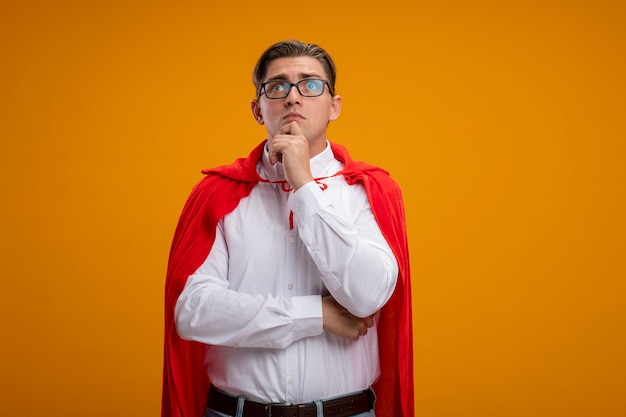 オレンジ色の背景の上に立って困惑して脇を見ている赤いマントとメガネのスーパーヒーローの実業家