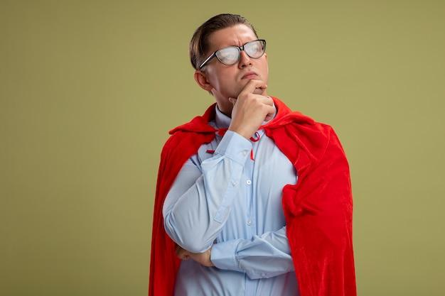 明るい壁の上に立って考えているあごに手を置いて脇を見て赤いマントと眼鏡のスーパーヒーローの実業家