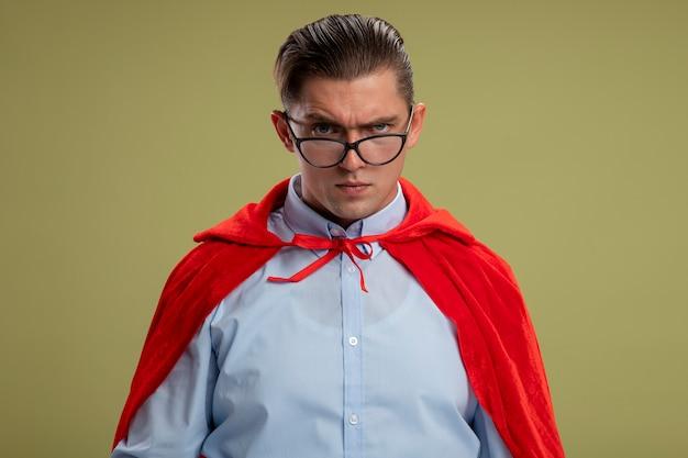 明るい背景の上に立っている深刻な眉をひそめている顔でカメラを見て赤いマントとメガネのスーパーヒーローの実業家