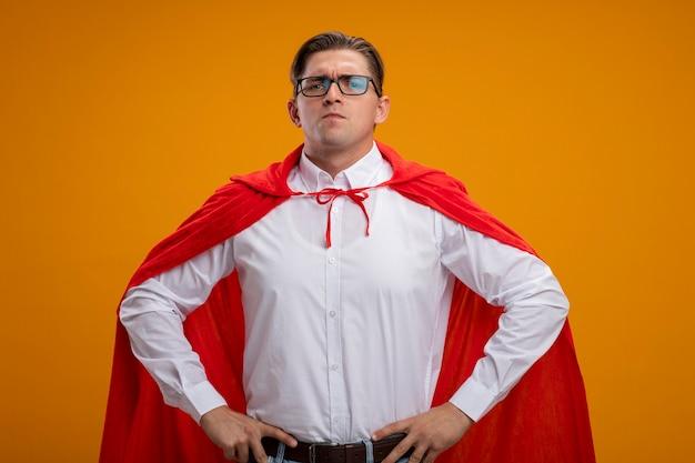 オレンジ色の背景の上に立っているヒップで腕に自信を持って見える赤いマントとメガネのスーパーヒーローの実業家