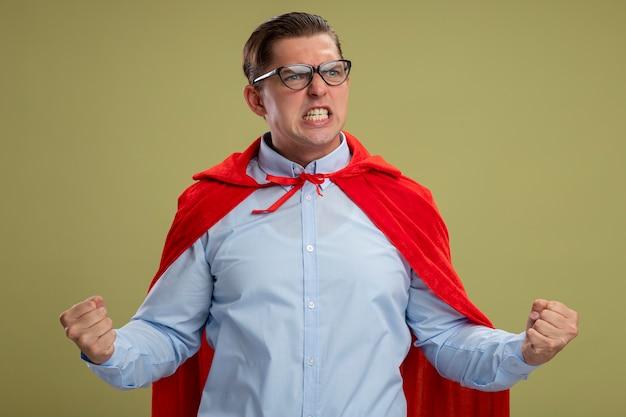 赤いマントとメガネのスーパーヒーローの実業家は、明るい背景の上に立って野生に行く拳を食いしばって怒っている表情で見て