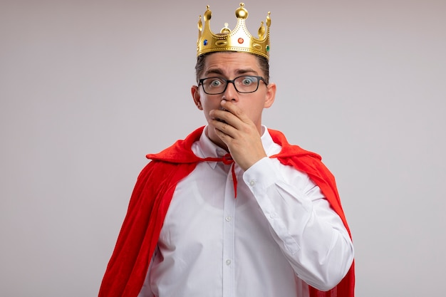 빨간 망토와 왕관을 쓰고있는 슈퍼 영웅 사업가 흰색 벽 위에 서있는 손으로 입을 덮고 놀란 놀라움