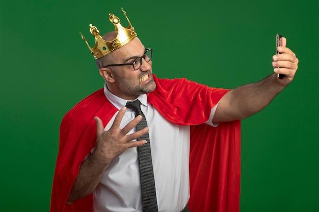 赤いマントと眼鏡をかけたスーパーヒーローのビジネスマンが、緑の壁の上に立って、スマートフォンを使って自分撮りをしています