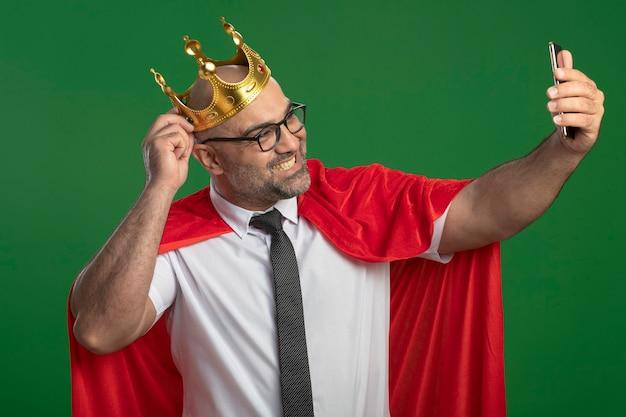 赤いマントと眼鏡をかけて、スマートフォンの笑顔を使用して自分撮りをしている王冠を身に着けているスーパーヒーローの実業家