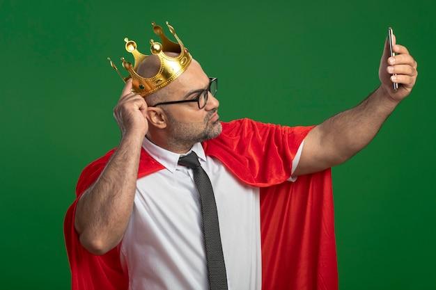 スマートフォンを使用してselfieを行う赤いマントと王冠を身に着けている眼鏡のスーパーヒーローの実業家
