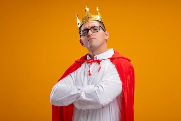 オレンジ色の背景の上に立っている胸に交差した腕に満足しているカメラを見て、赤いマントと眼鏡をかけたスーパーヒーローのビジネスマン