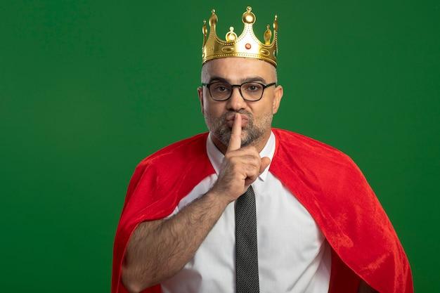 緑の壁の上に立っている唇に指で沈黙のジェスチャーを作る王冠を身に着けている赤いマントと眼鏡のスーパーヒーローの実業家