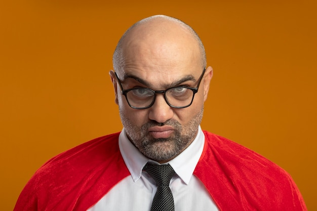 眉をひそめている顔でカメラを見て不機嫌な赤いマントとメガネのスーパーヒーローの実業家