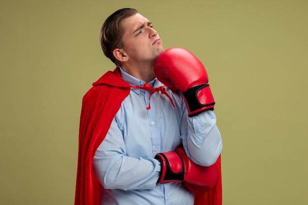 赤いマントとボクシンググローブのスーパーヒーローのビジネスマンは、明るい壁の上に立っている彼のあごに手で顔に物思いにふける表情で脇を見て