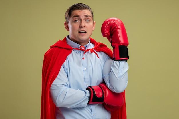 赤いマントとボクシンググローブでカメラを見てスーパーヒーローの実業家は、明るい背景の上に立っている上げられた手と混同