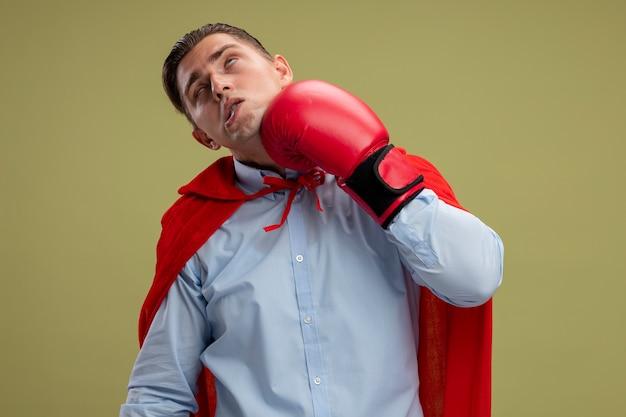 赤いマントとボクシンググローブで明るい背景の上に立って自分自身をパンチするスーパーヒーローのビジネスマン