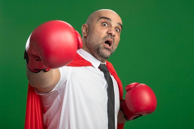빨간 망토와 권투 장갑에 슈퍼 영웅 사업가 정면을보고 손을 올리는 것은 녹색 벽 위에 서있는 소리를 무서워