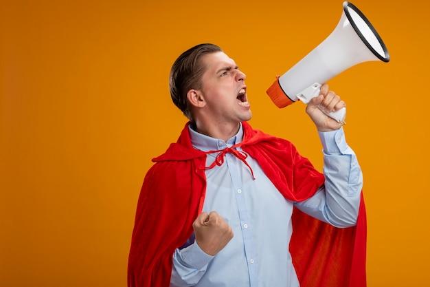 Супергерой бизнесмен в красной накидке, сжимающий кулак, кричит в мегафон с агрессивным выражением лица, стоя над оранжевой стеной