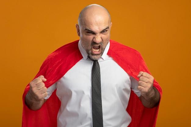オレンジ色の壁の上に立って叫んで拳を握りしめている赤いマントのスーパーヒーローの実業家