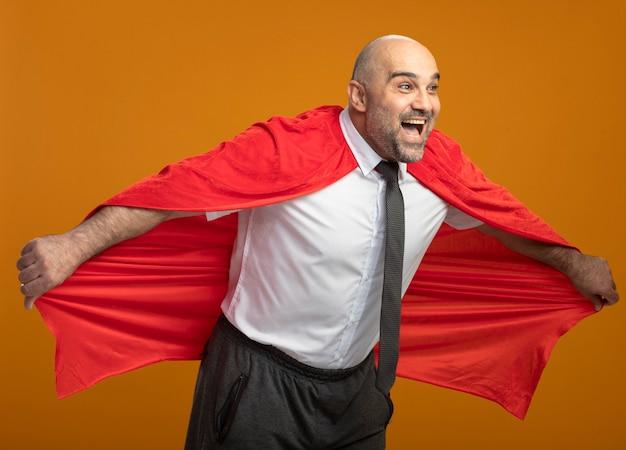 赤いマントを着たスーパーヒーローのビジネスマンが幸せで前向きにマントを持って飛ぶ