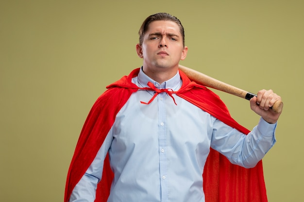 明るい壁の上に立っている深刻な自信を持って表情で野球のバットを保持している赤いマントのスーパーヒーローの実業家