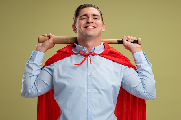 明るい壁の上に立って自信を持って笑って首の後ろに保持している赤いマントのスーパーヒーローの実業家