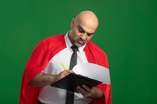 Бизнесмен супергероя в красном плаще держит буфер обмена с пустыми страницами, пишет что-то с серьезным лицом, стоящим над зеленой стеной
