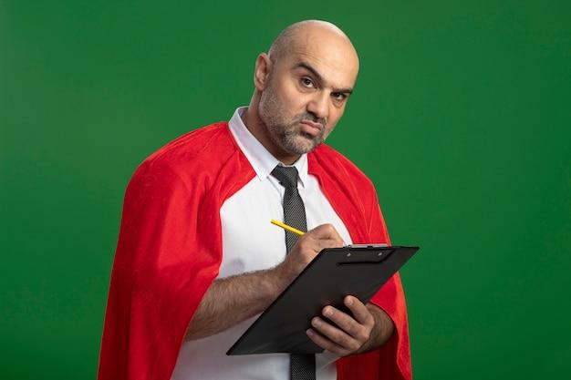 Бизнесмен супергероя в красном плаще держит буфер обмена, что-то пишет с серьезным лицом, стоящим над зеленой стеной
