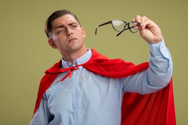 Супергерой бизнесмен в красном плаще держит очки, с интересом смотрит на них, стоя на светлом фоне