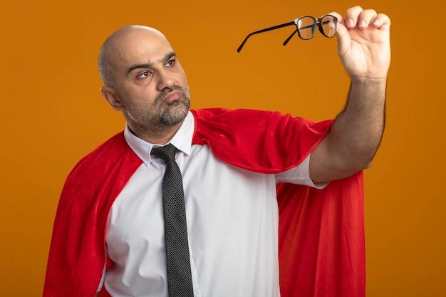 真面目な顔でそれらを見ている彼の眼鏡を保持している赤いマントのスーパーヒーローの実業家