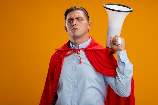 Бизнесмен супергероя в красном плаще держит мегафон с серьезным хмурым лицом, стоящим над оранжевой стеной
