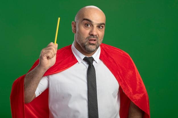 鉛筆を持っている赤いマントのスーパーヒーローの実業家は、新しいアイデアを持って驚いた
