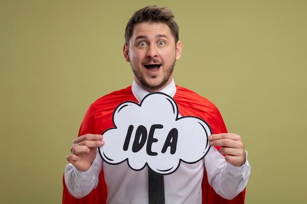 Бизнесмен супергероя в красном мысе, держащий знак речи пузырь с идеей слова, смотрящий в камеру, изумлен и удивлен счастливой улыбкой, стоя на зеленом фоне