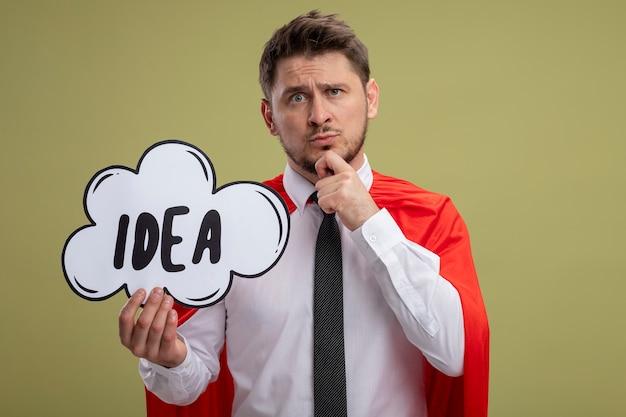 녹색 배경 위에 의아해 서 찾고 단어 아이디어와 연설 거품 기호를 들고 빨간 케이프에서 슈퍼 영웅 사업가