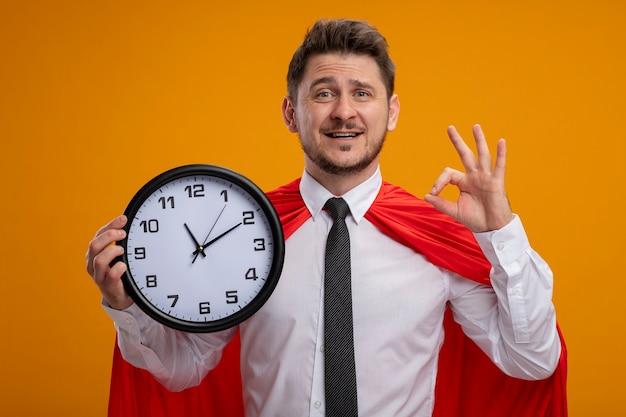 オレンジ色の背景の上に立っているokのサインを元気に見せて笑顔のカメラを見て壁時計を保持している赤い岬のスーパーヒーローの実業家