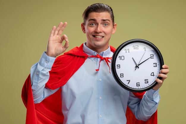 明るい背景の上に立っているokサインを示しているカメラの笑顔を見て壁時計を保持している赤いマントのスーパーヒーロー
