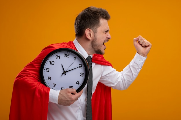 Супергерой бизнесмен в красном плаще держит настенные часы спешит, готов помочь, стоя на оранжевом фоне