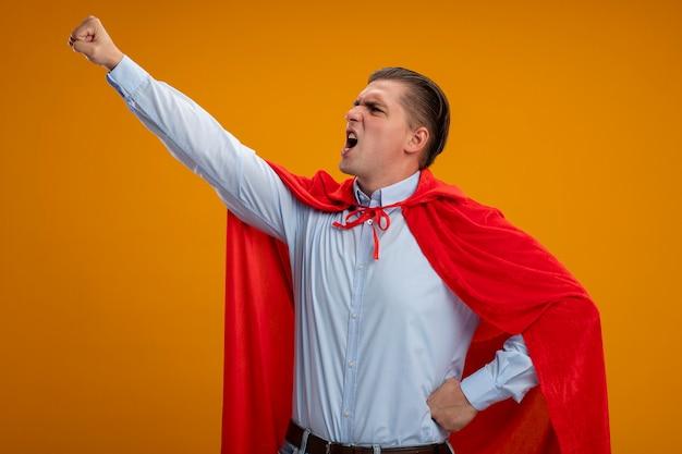 オレンジ色の背景の上に立って戦う準備ができて叫んで飛んでいるジェスチャーで腕を保つ赤いマントのスーパーヒーローの実業家
