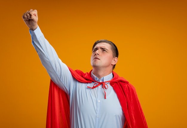 オレンジ色の背景の上に立っている飛行ジェスチャーで腕を脇に見ている赤いマントのスーパーヒーローの実業家