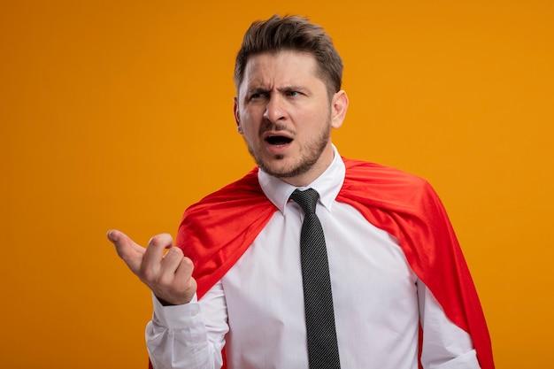 オレンジ色の背景の上に立って混乱していることを求めて腕を出して脇を見て赤いマントのスーパーヒーローの実業家