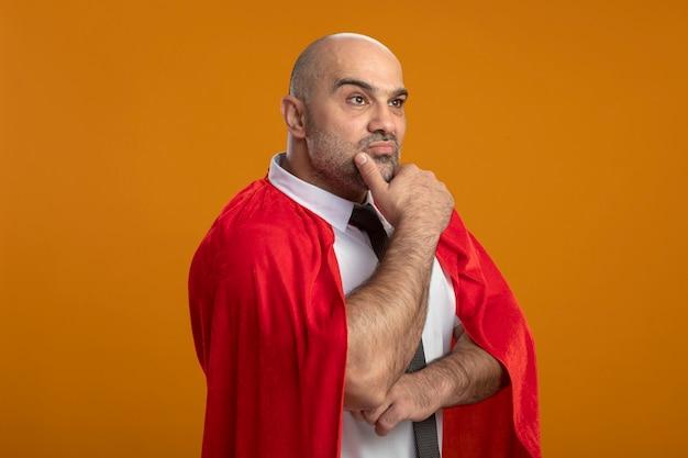 オレンジ色の壁の上に立って物思いにふける表情を考えてあごに手を脇に見ている赤いマントのスーパーヒーローの実業家