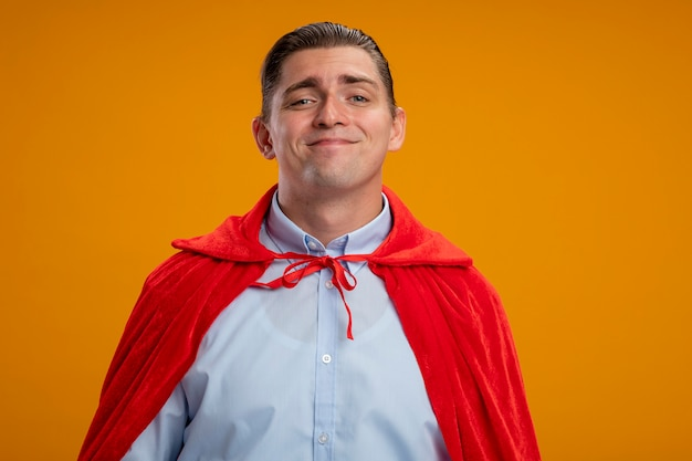 オレンジ色の背景の上にフレンドリーな立って笑顔のカメラを見て赤いマントのスーパーヒーロービジネスマン