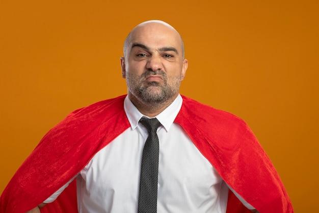 オレンジ色の壁の上に立って不機嫌になっている正面を見て赤いマントのスーパーヒーローの実業家