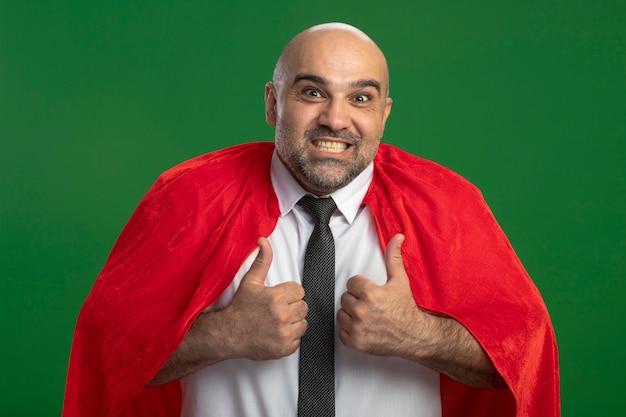 녹색 벽 위에 서 엄지 손가락을 보여주는 전면 행복하고 긍정적 인 미소를보고 빨간 케이프에서 슈퍼 영웅 사업가
