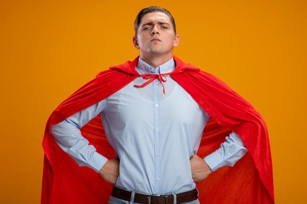 オレンジ色の背景の上に立つのを助ける準備ができて腰に腕を持つ深刻な顔に自信を持って見える赤いマントのスーパーヒーローの実業家