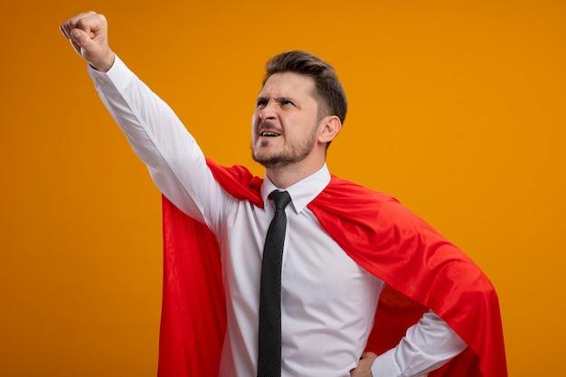 오렌지 배경 위에 서있는 데 도움이 될 준비가 승리 제스처를 만드는 찾고 빨간 케이프에서 슈퍼 영웅 사업가