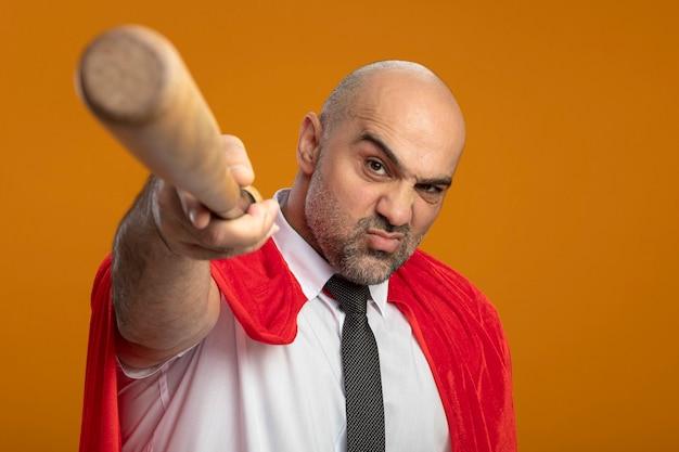 怒った顔で見てカメラで野球のバットを指している赤いマントのスーパーヒーローの実業家